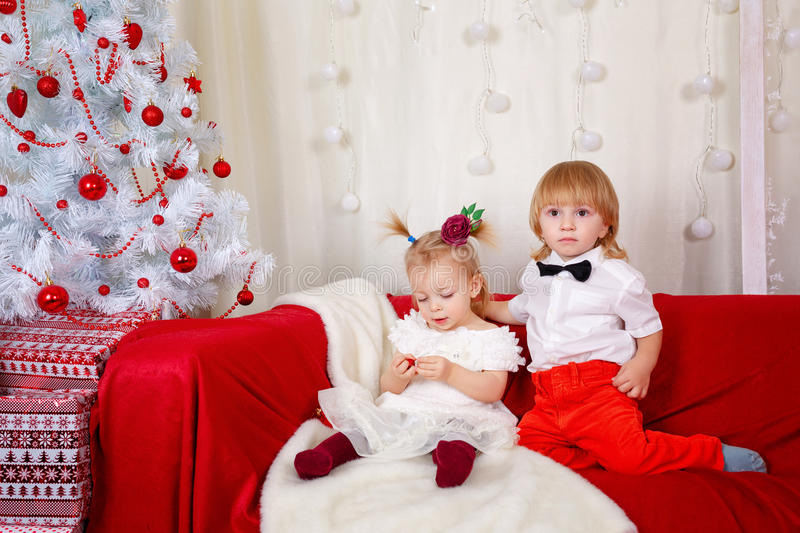 Brother and sister awaiting Christmas. Little brother and sister sitting on the couch near Christmas tree royalty free stock photo