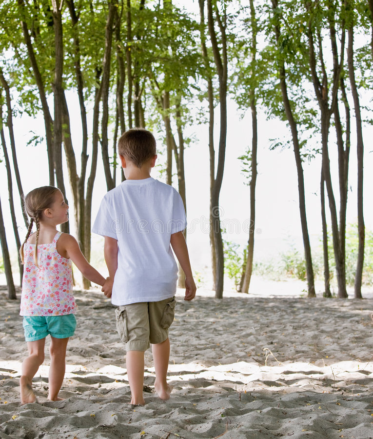 Brother and sister at beach stock images