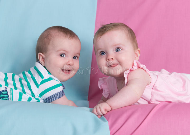 Brother and sister. Beautiful twins on pink and blue.Brother and sister stock photo