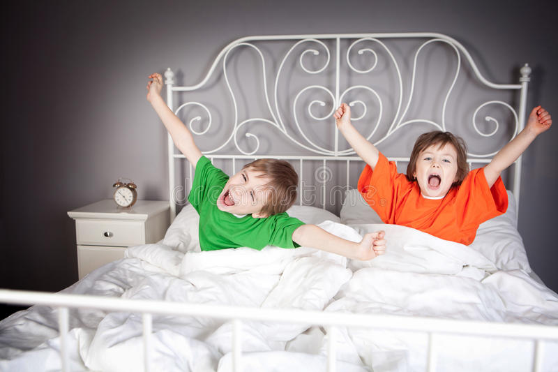 Brother and Sister in bed. Brother and Sister awakening, yawning and their arms outstretched, in their parents double bed stock image