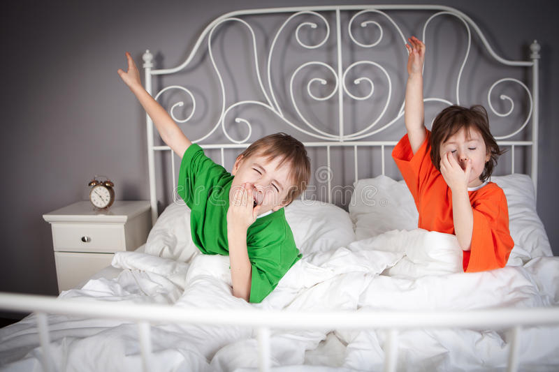 Brother and Sister in bed. Brother and Sister awakening, yawning and their arms outstretched, in their parents double bed royalty free stock photography