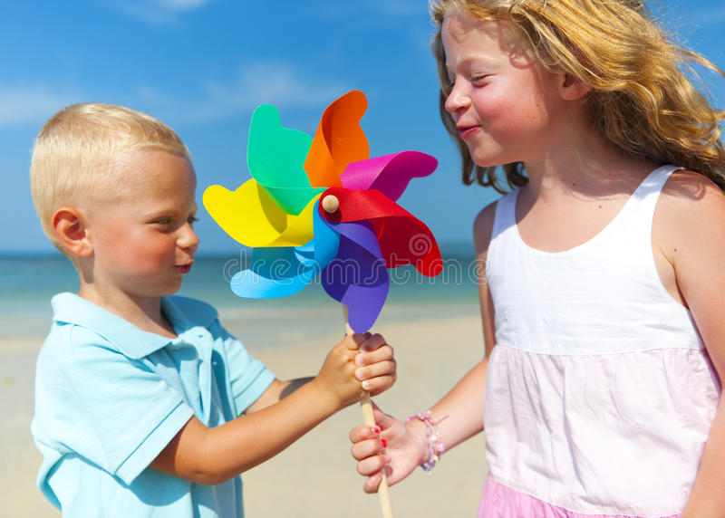 Brother sister blowing windmill beach Concept.  stock images