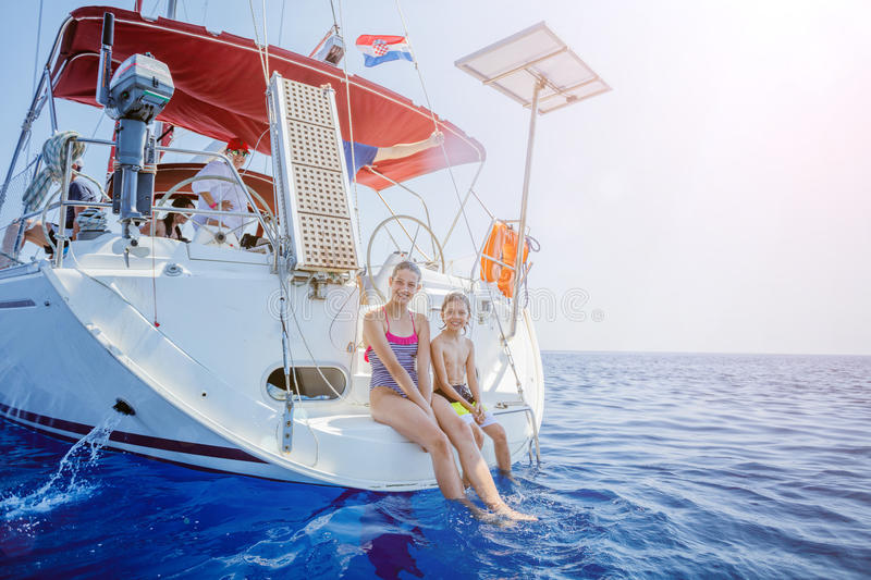 Brother and sister on board of sailing yacht on summer cruise. Travel adventure, yachting with child on family vacation. stock image