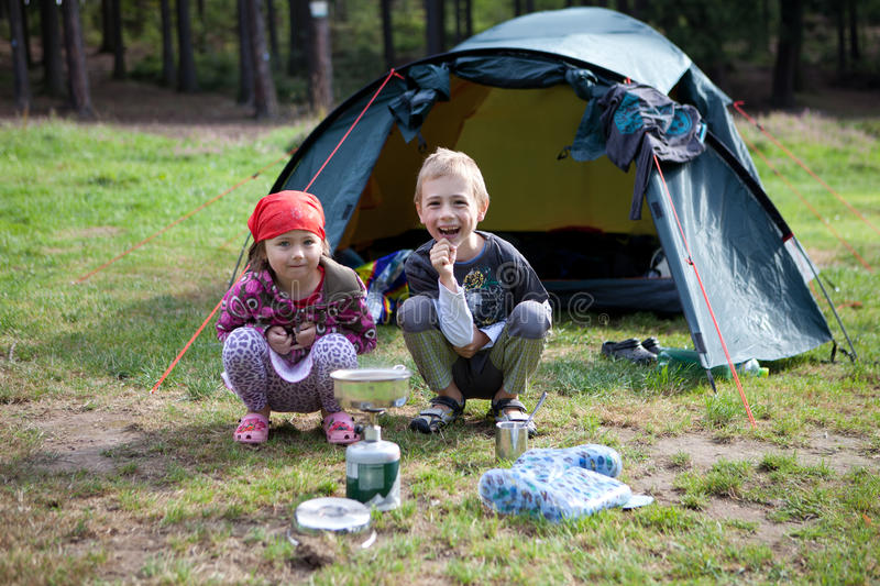 Brother and Sister camping. Young children, brother and sister, crouching down outside an open blue tent in a field on the edge of a forest with a gas container royalty free stock photo