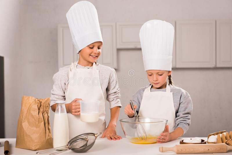 Brother and sister in chef hats and aprons whisking eggs in bowl at table. In kitchen royalty free stock images