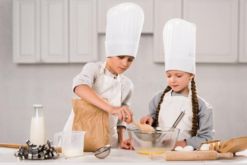 Brother and sister in chef hats and aprons whisking eggs in bowl at table. In kitchen royalty free stock photos