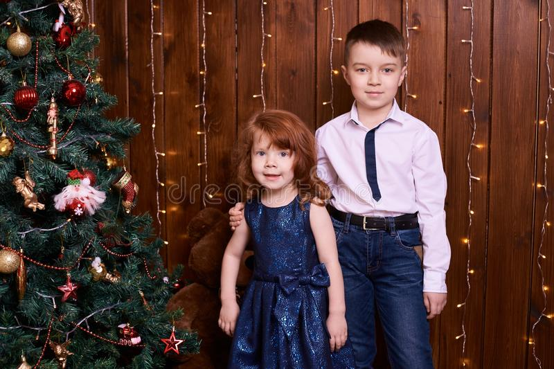 Brother and sister. Christmas interior. Small children. Family portrait. Brown background stock photo