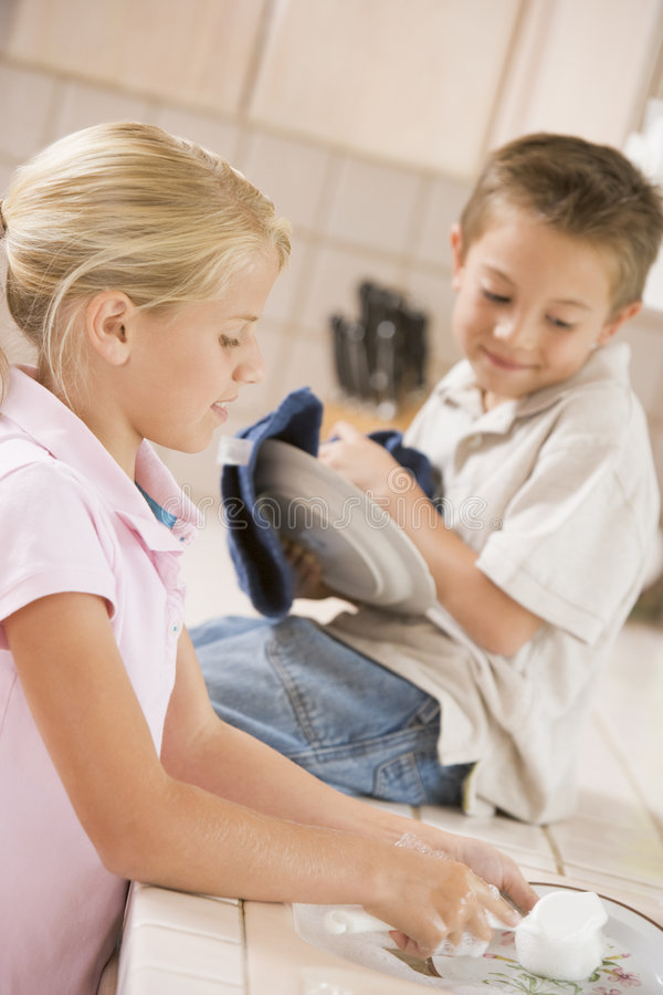 Brother And Sister Cleaning Dishes Together stock images