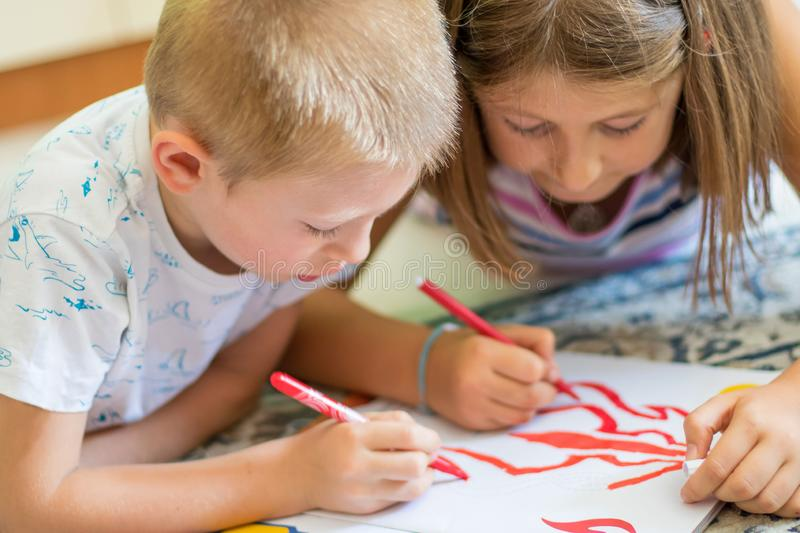 Brother and sister drawing on floor on paper. Preschool boy and girl play on floor with pencil and paper royalty free stock images