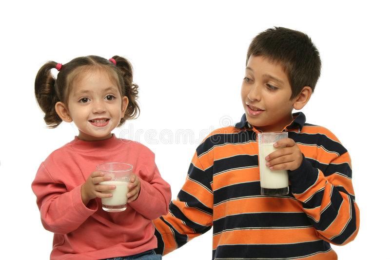 Brother and sister drinking mi. Children drinking a fresh glass of milk together royalty free stock photography