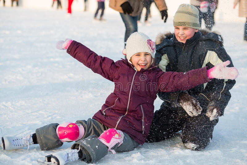 Brother and sister fell while skating and playing. With snow royalty free stock images