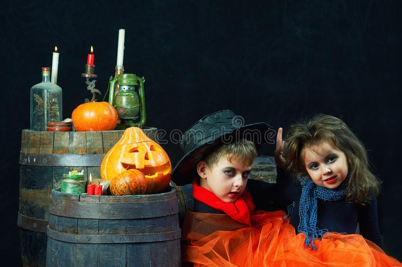 Brother and sister on Halloween. Funny kids in carnival costumes on dark background . stock photography