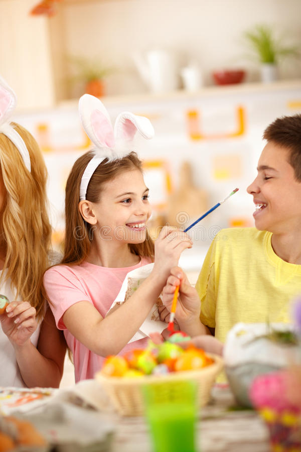 Brother and sister having fun while painting Easter eggs. Cheerful brother and sister having fun while painting Easter eggs stock photos