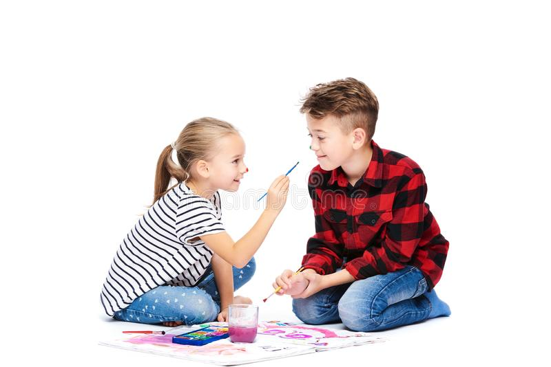 Brother and sister having fun painting with watercolors. Happy creative children at art class. Art therapy concept. Brother and sister having fun painting with stock image