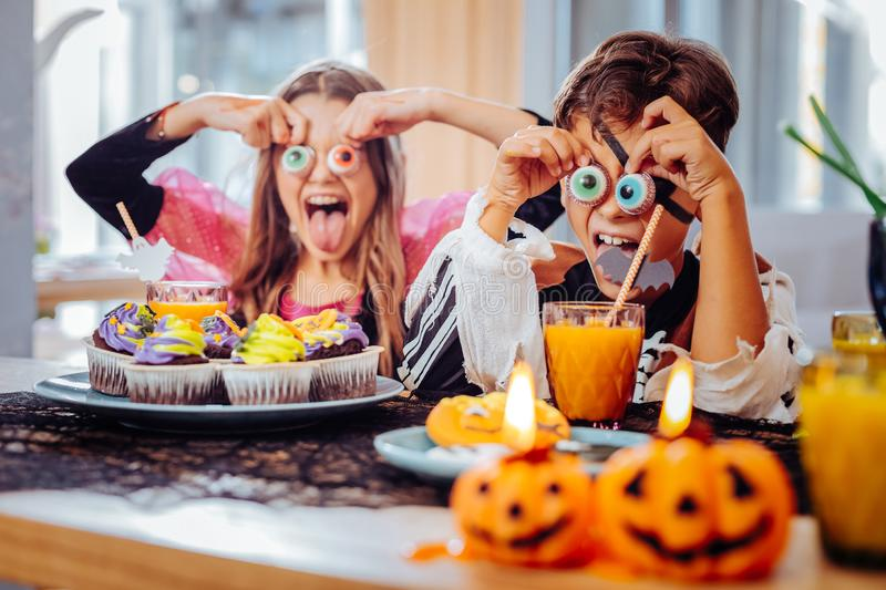 Brother and sister having Halloween party eating thematic cookies. Thematic cookies. Good-looking funny brother and sister having Halloween party having fun royalty free stock image
