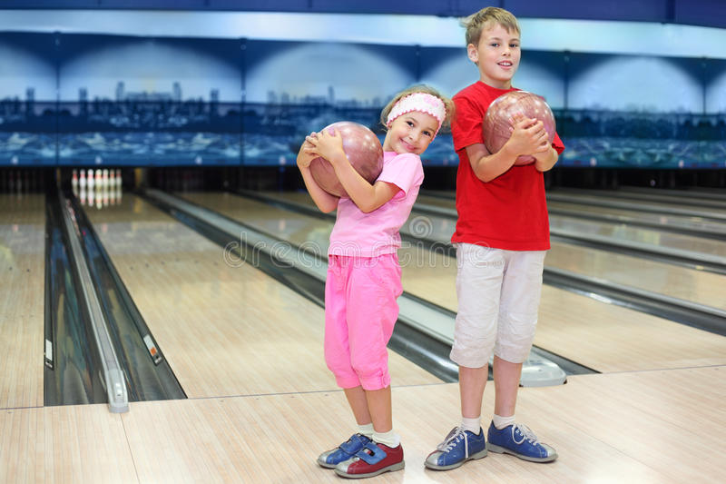 Brother and sister hold balls in bowling club
