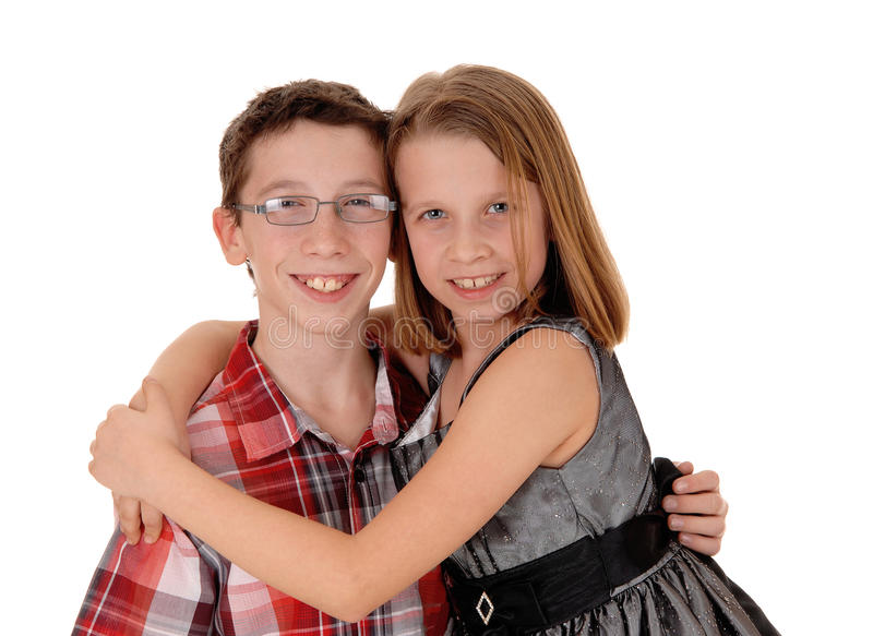 Brother and sister hugging. A little sister is hugging her older brother, isolated on white background royalty free stock photos