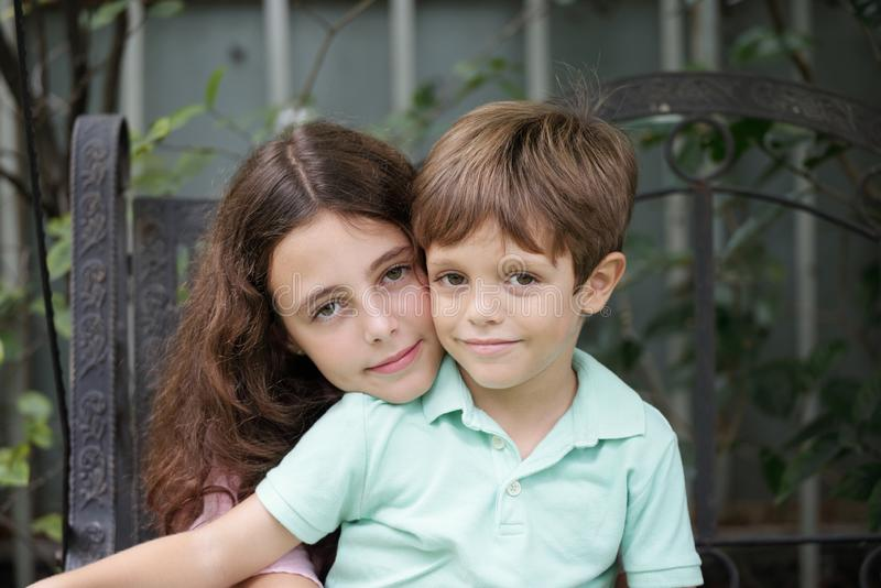 c247b1426b8073 Brother and sister. Hugging smiling brother and sister looking at camera  stock photo
