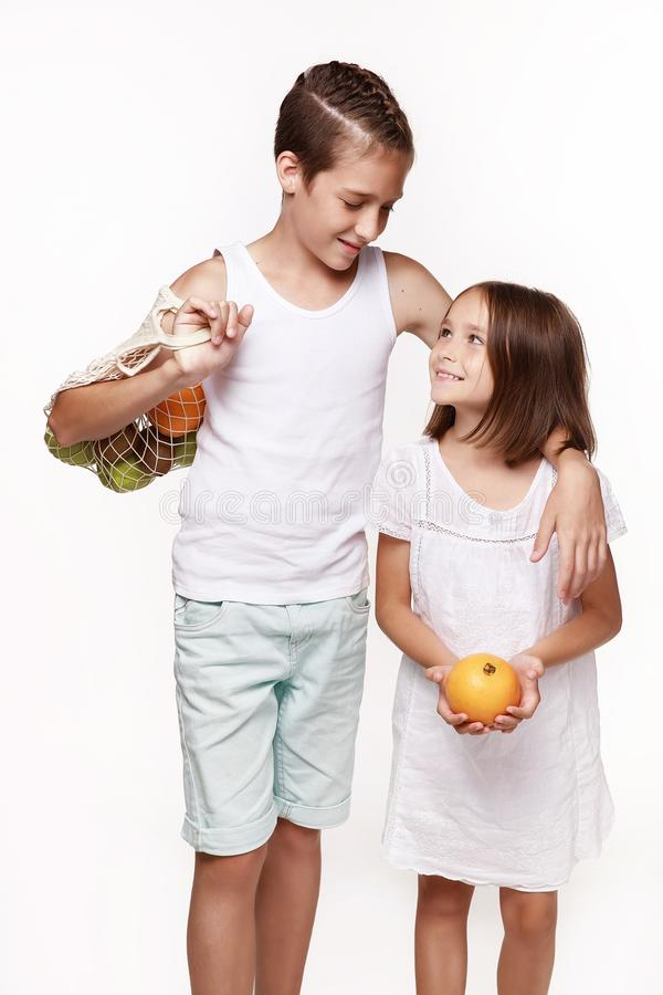 Brother and sister in light clothes with fruit on a white background, in the studio. stock image
