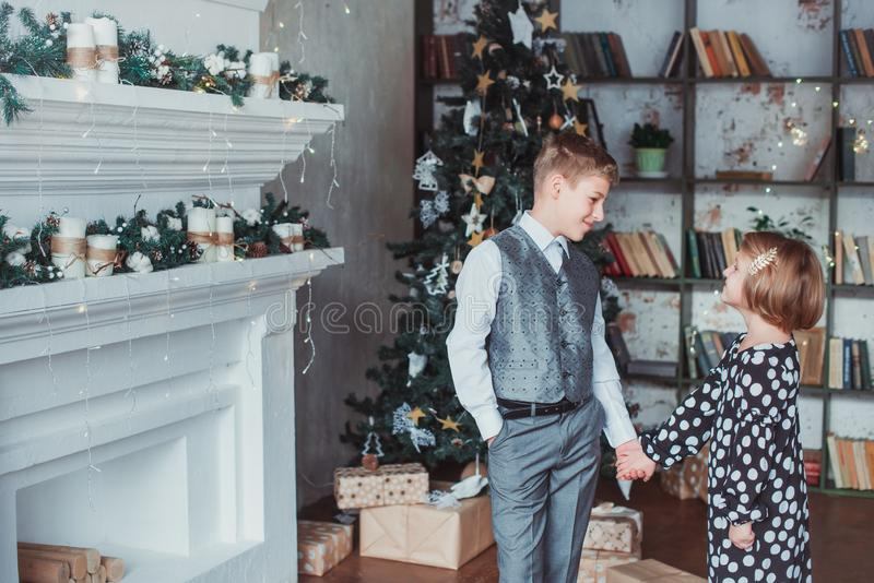 Brother and sister in the living room in the background of the Christmas tree. Children festively dressed royalty free stock photography