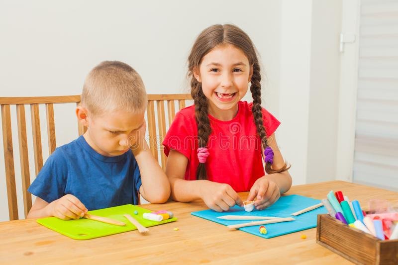 Brother and sister molding at the table royalty free stock photos