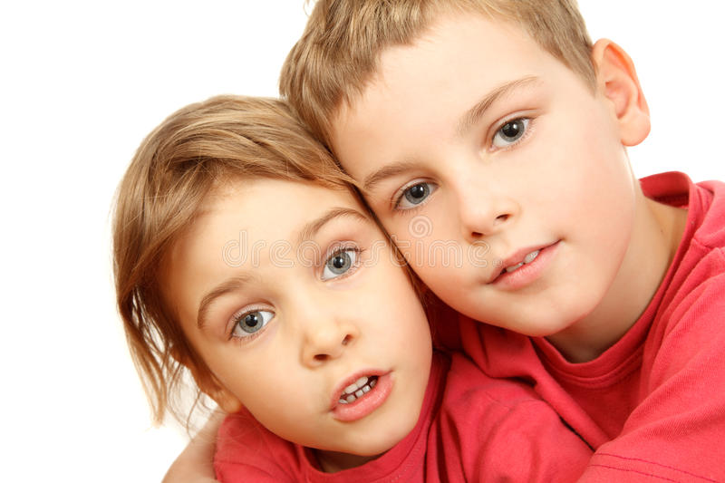 Brother And Sister In Pink Shirts Embracing Stock Photography