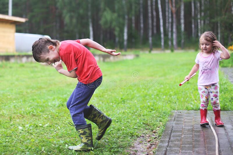 Brother and sister play in rainy weather Children jump in puddle and mud in the rain. stock images