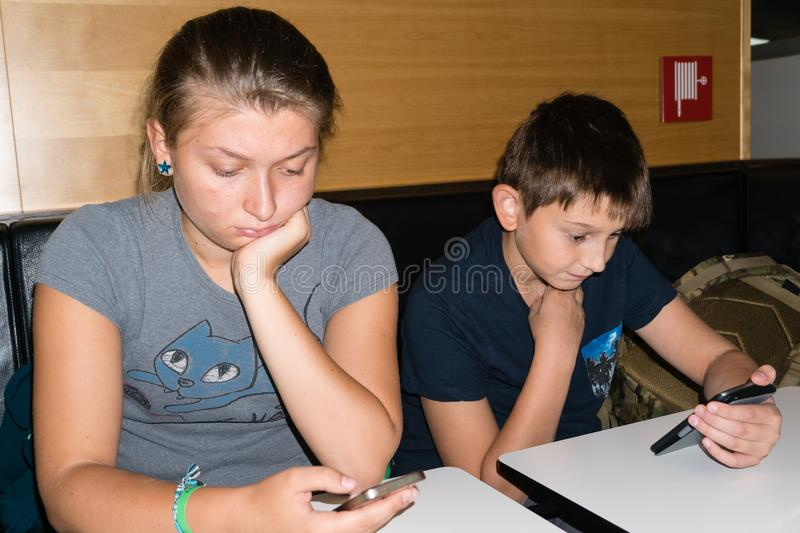 Brother and sister play with a smartphone waiting to have lunch royalty free stock photos