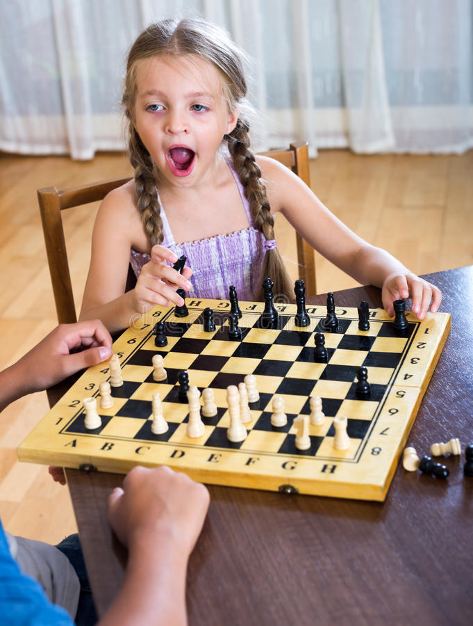 Brother and sister playing chess stock images