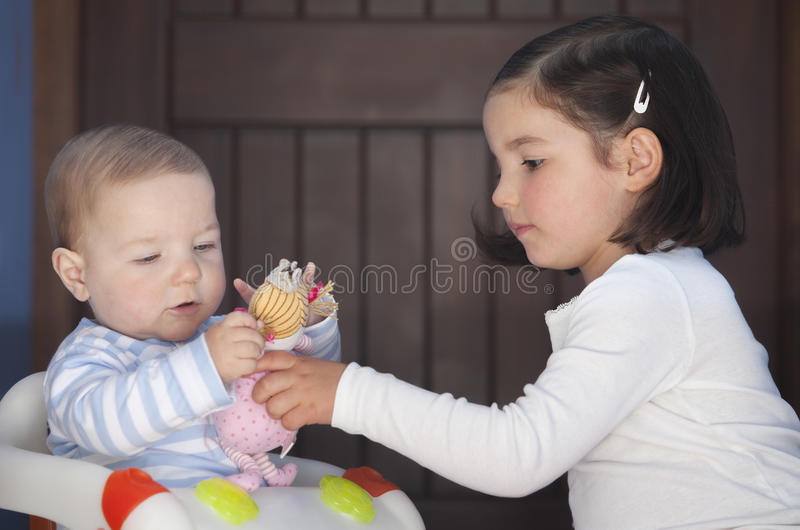 Brother and sister playing with dolls. Sex stereotyping overcome royalty free stock photography