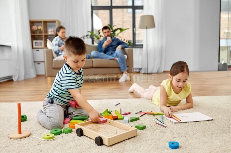 Brother and sister playing and drawing at home stock photography