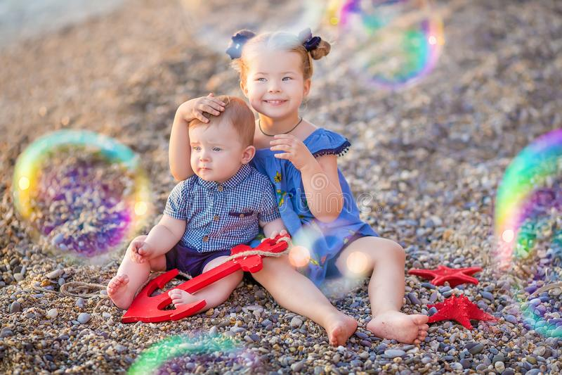 Brother and sister playing in the shore break on the beach during the hot summer vacation day with bubles royalty free stock images