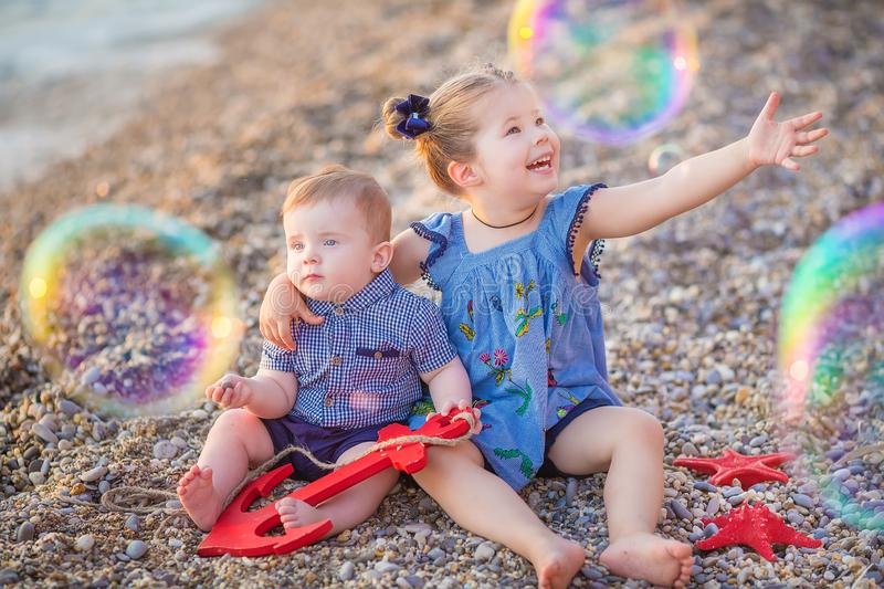 Brother and sister playing in the shore break on the beach during the hot summer vacation day with bubles royalty free stock photography