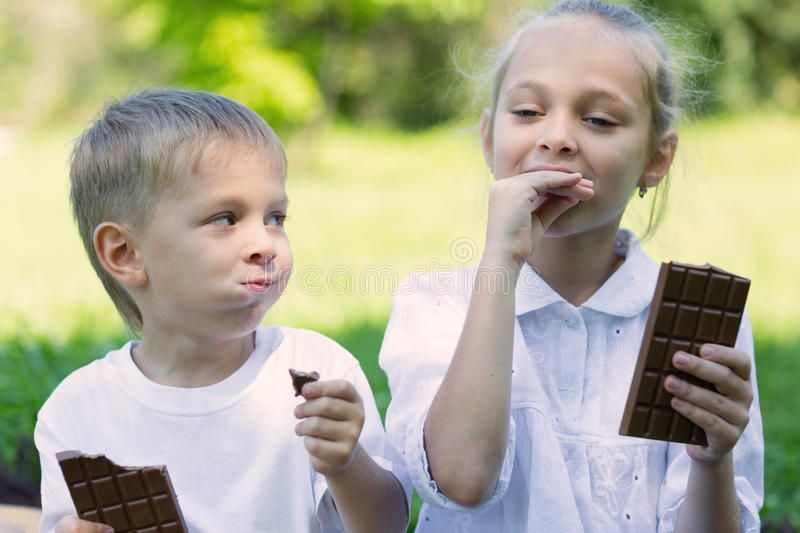 Brother and sister with relish eating chocolate. Outdoors stock photos