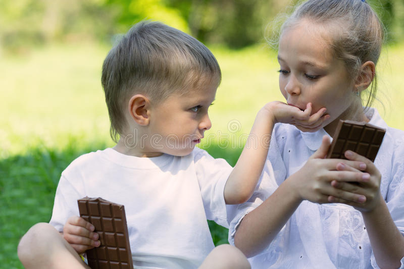 Brother and sister with relish eating chocolate. Outdoors royalty free stock images
