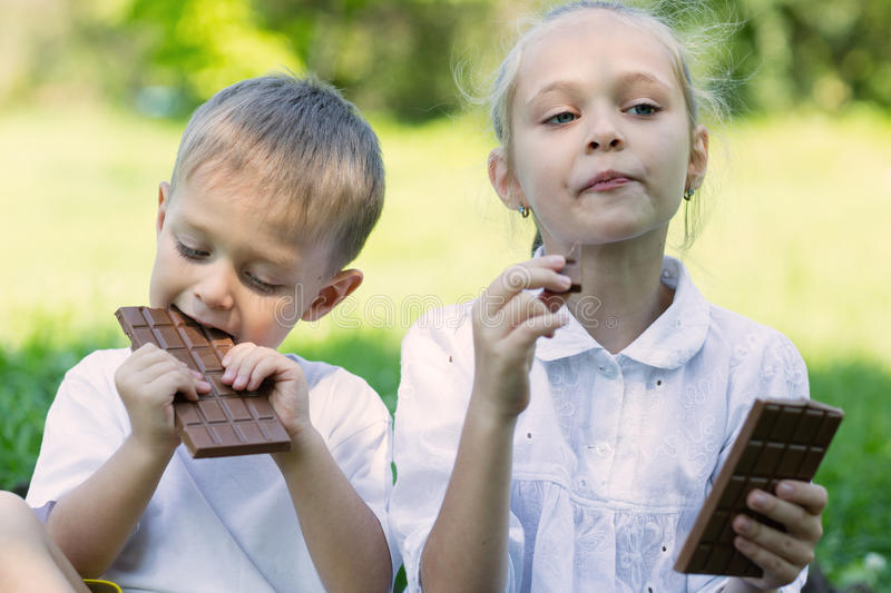 Brother and sister with relish eating chocolate. Outdoors. Summer park stock photo