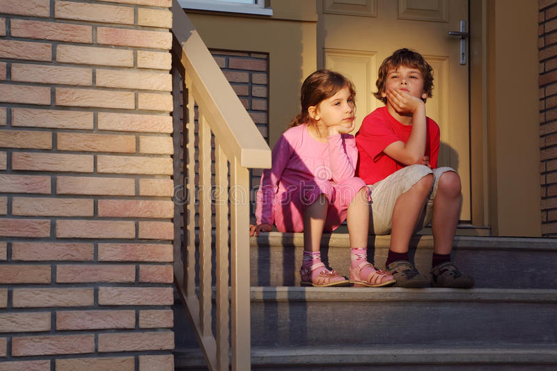 Brother and sister sit on stairs