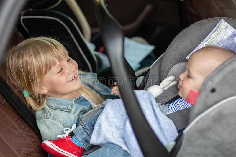 Brother and sister sitting in car in safety seat. Siblings on passenger places having fun together during travel by stock image