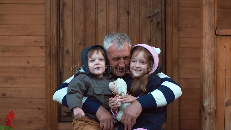 Brother and sister sitting on the grandfather s knees. Old man hugs his grandson and granddaughter. 4K royalty free stock photos