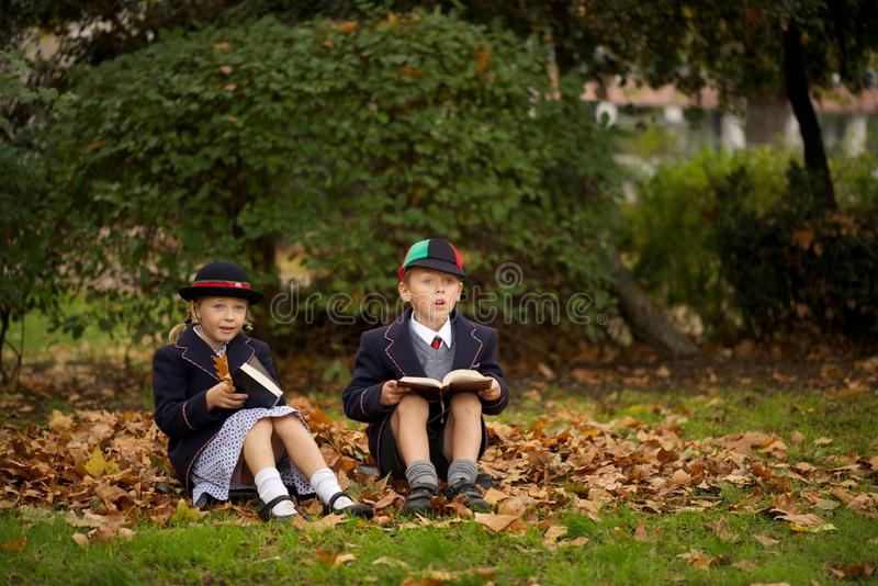 Brother and sister sitting reading among leaves royalty free stock photography