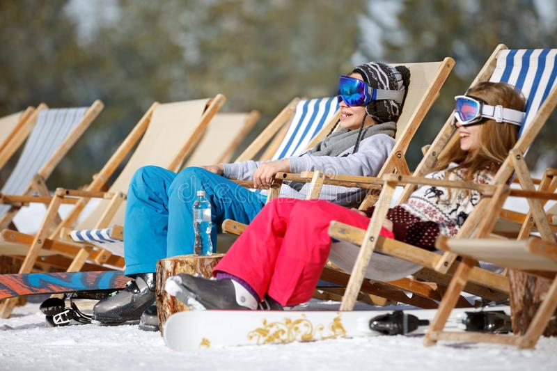 Brother and sister sitting in sun loungers. On ski terrain royalty free stock photo