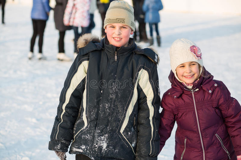 Brother and sister skating hand in hand stock photography