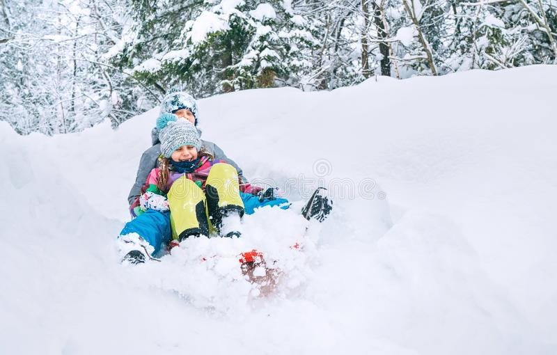 Brother and sister slide down together from snow slope in forest. Winter activities concept image royalty free stock photo