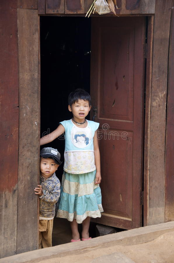 Brother and sister stand in doorway in the village stock photography