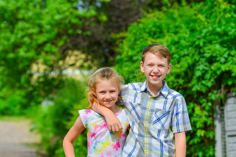 Brother and sister stand in an embrace in the park on the street and look at each other. The concept of happiness, family, love,. Unity and joy royalty free stock photography