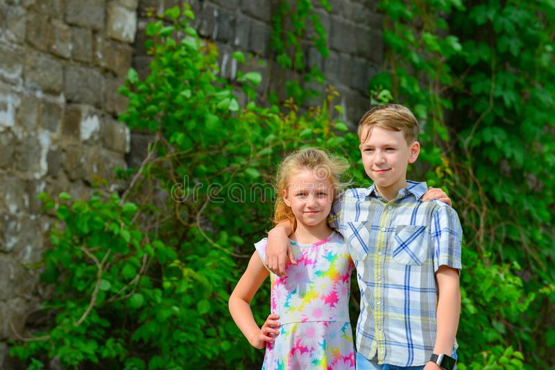 Brother and sister stand in an embrace in the park on the street and look at each other. The concept of happiness, family, love,. Unity and joy royalty free stock images
