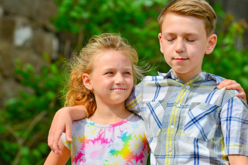 Brother and sister stand in an embrace in the park on the street and look at each other. The concept of happiness, family, love,. Unity and joy royalty free stock image