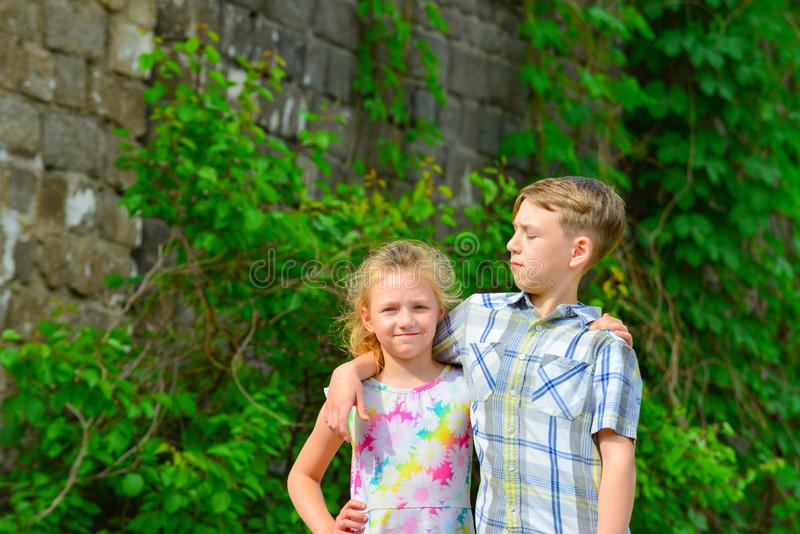 Brother and sister stand in an embrace in the park on the street and look at each other. The concept of happiness, family, love,. Unity and joy stock photos