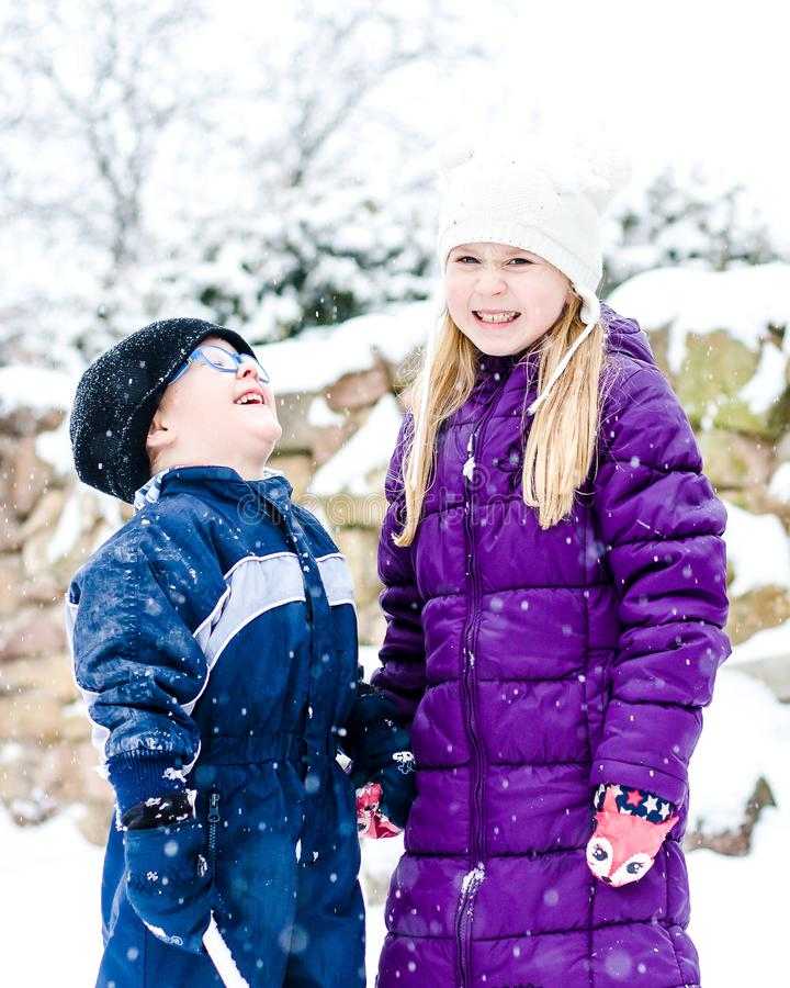Brother with sister are standing outside during falling snow. Smiling kids in winter. stock photography