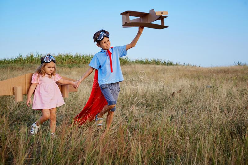 Brother and sister in suits of superhero pilots are walking in n stock images